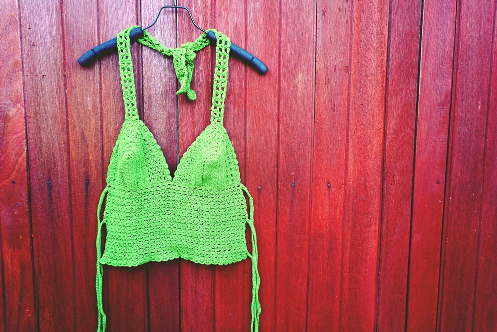 Green bikini top hang on brown wood background, summer beach and holiday concept