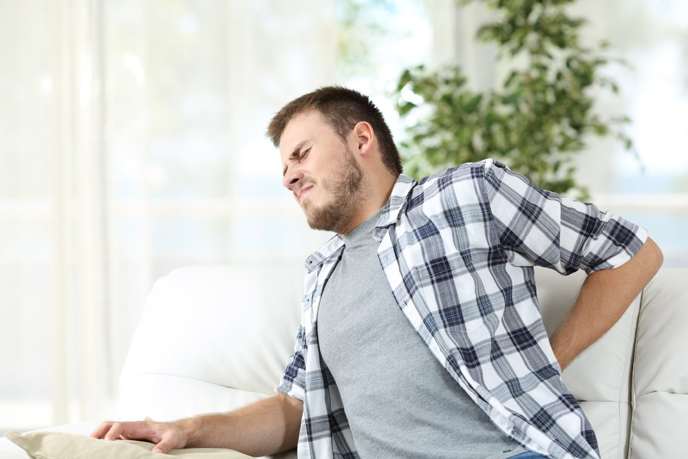 man experiencing back spasms in pain