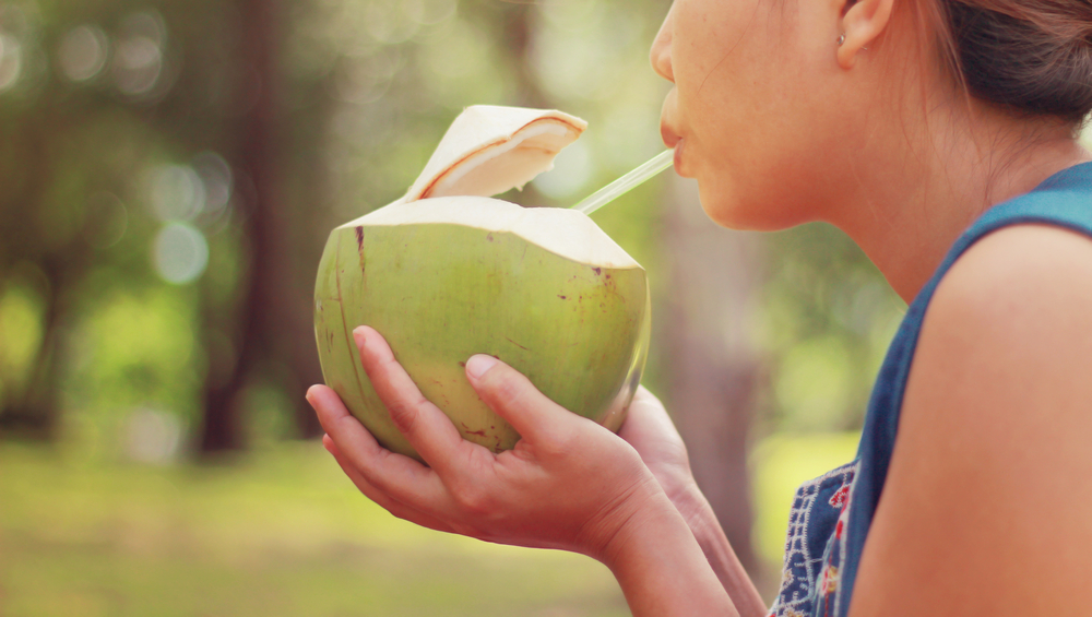young woman drinking out of a fresh young coconut