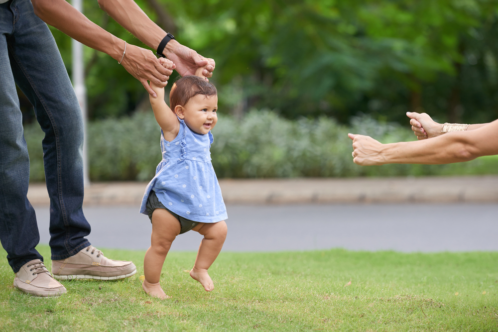 parents teaching their toddler to walk