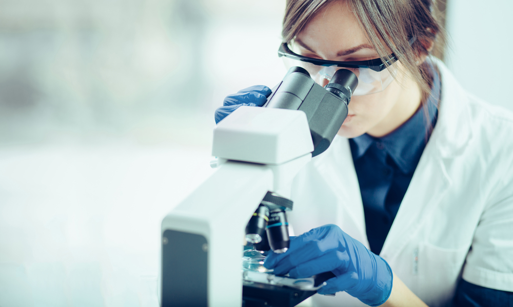 female researcher looking into a microscope at a petri dish