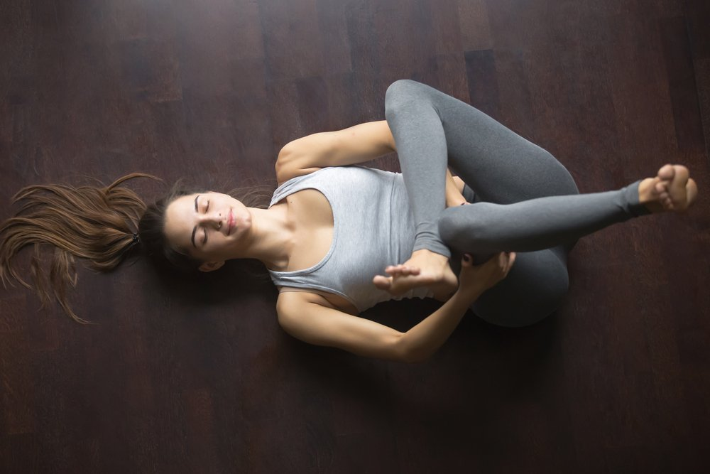young woman in reclined pigeon pose or eye of the needle pose