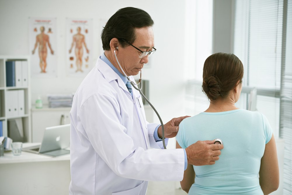 doctor checking patient's breathing with stethoscope