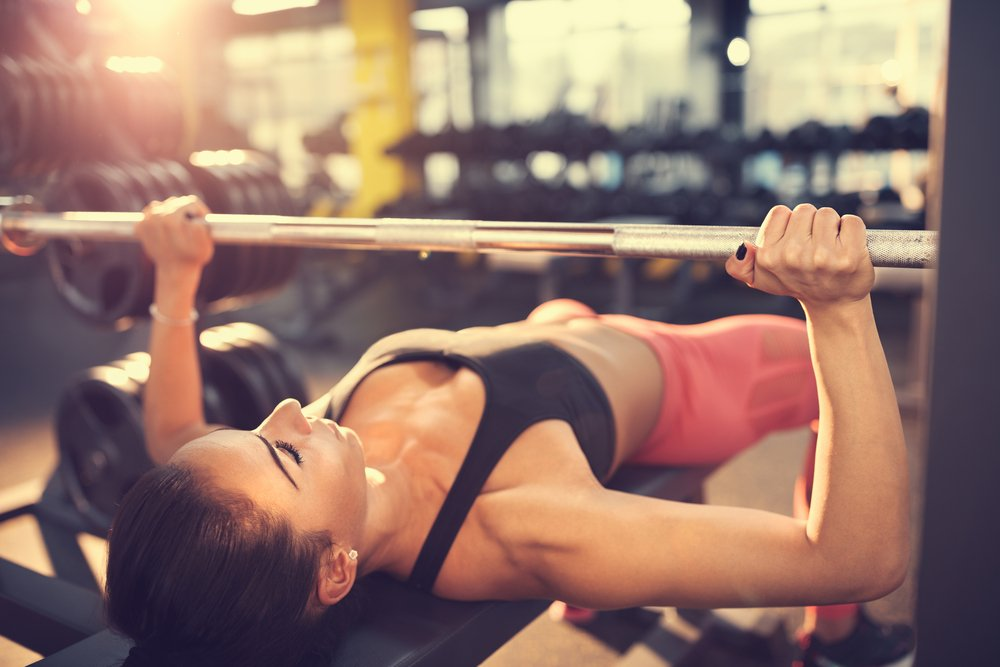 woman holding a barbell over her chest in a bench press at the gym