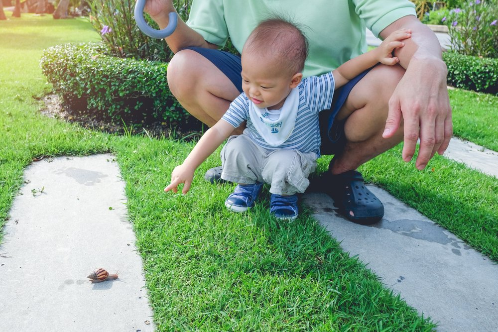 one year old baby pointing at a snail outside