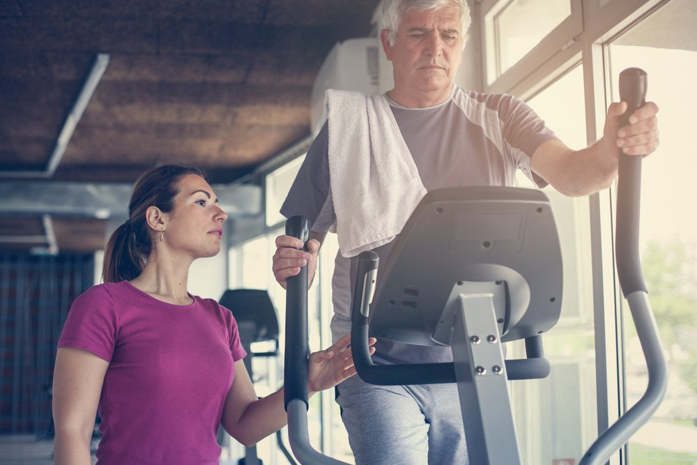 personal trainer helping an older man on an elliptical machine