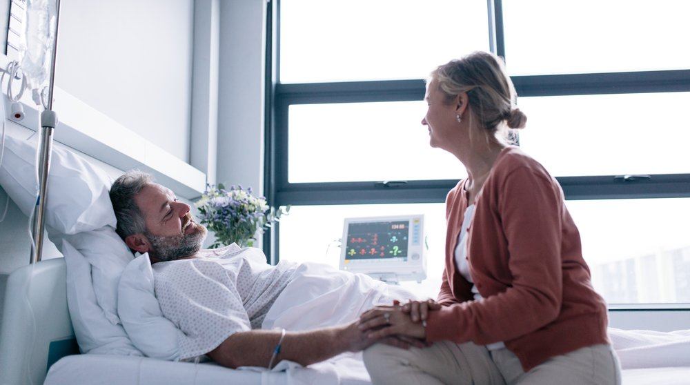 woman sitting with her sick husband in the hospital