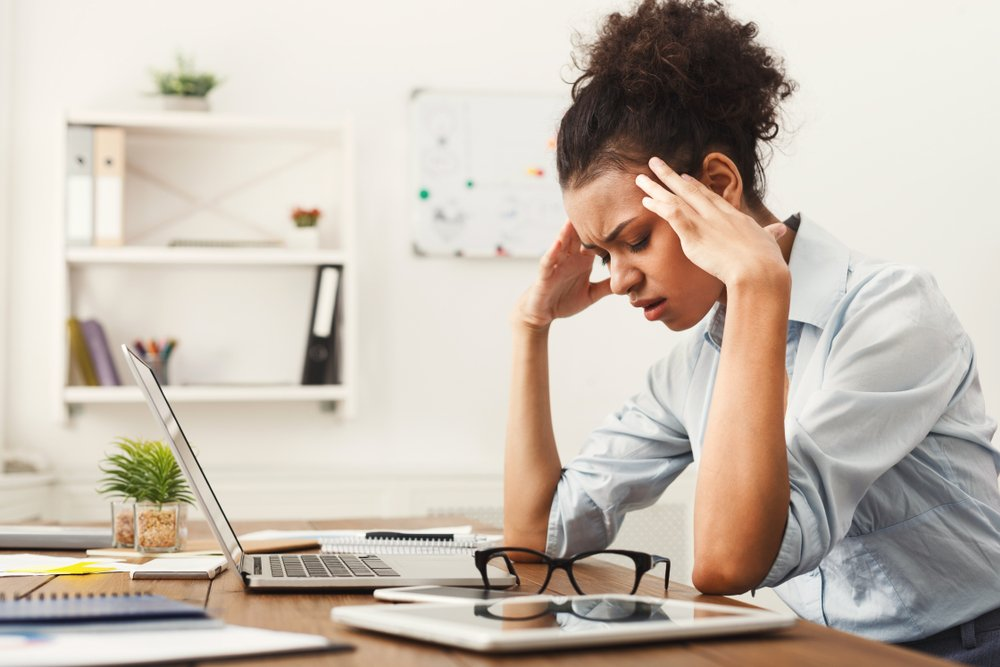woman at her desk suffering from a headache