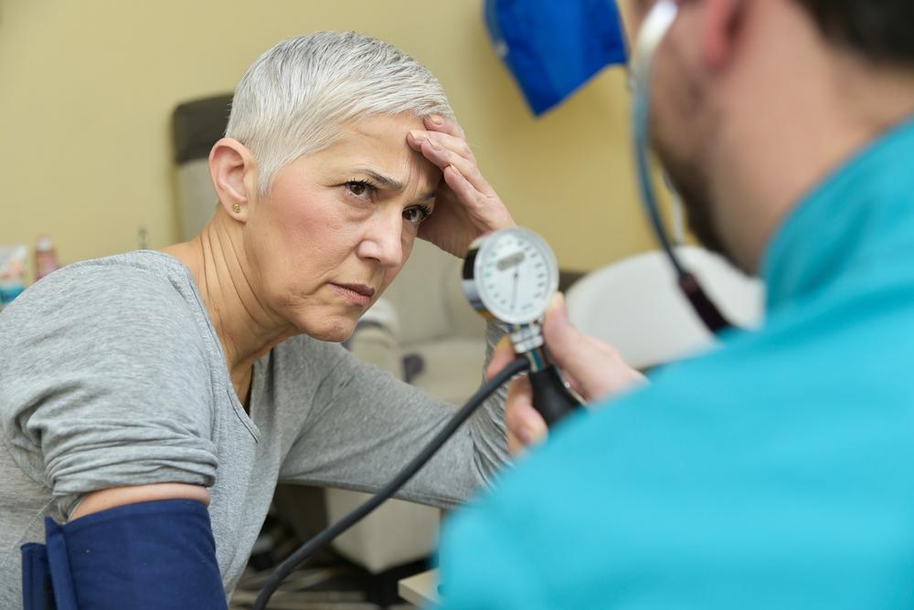 older woman looking concerned during blood pressure test