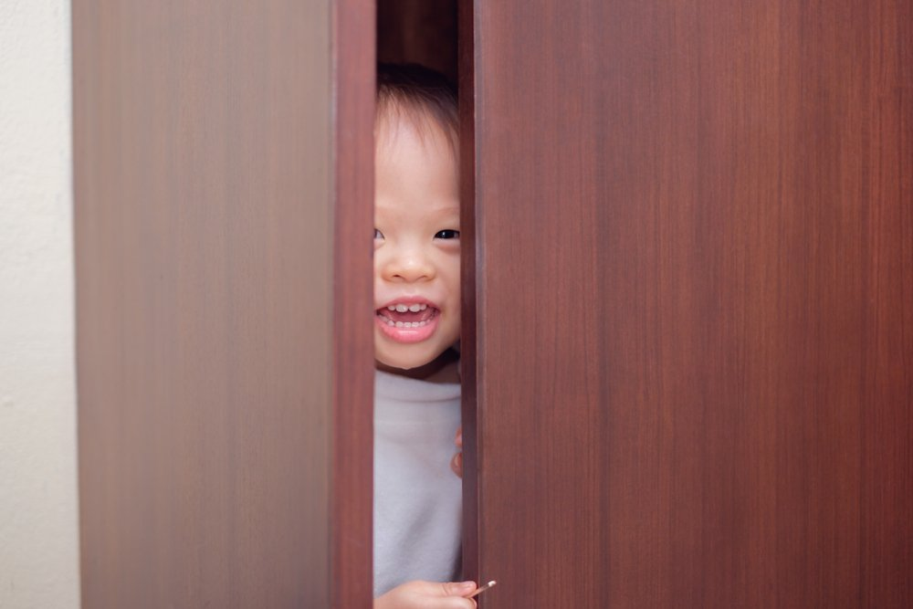 one year old baby playing hide and seek in a closet