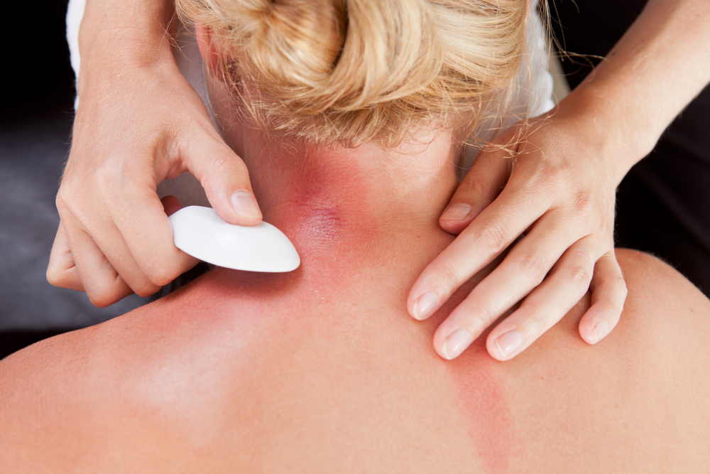 acupuncturist using gua sha tool on client's neck