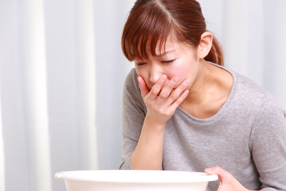 woman feeling nausea is leaning over a bowl