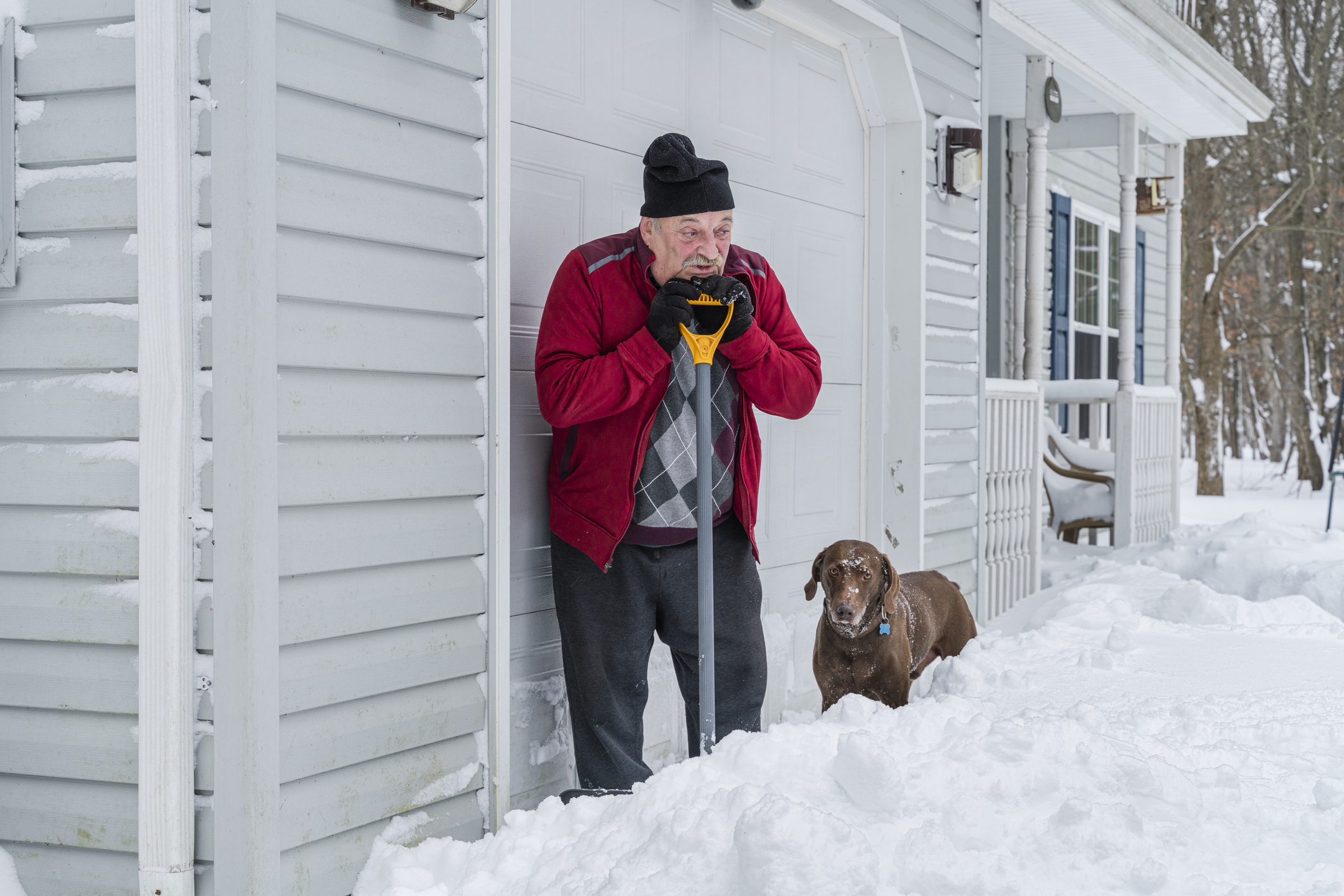 Senior retired Caucasian White man cleaning the snow around his home after the winter snowstorm.