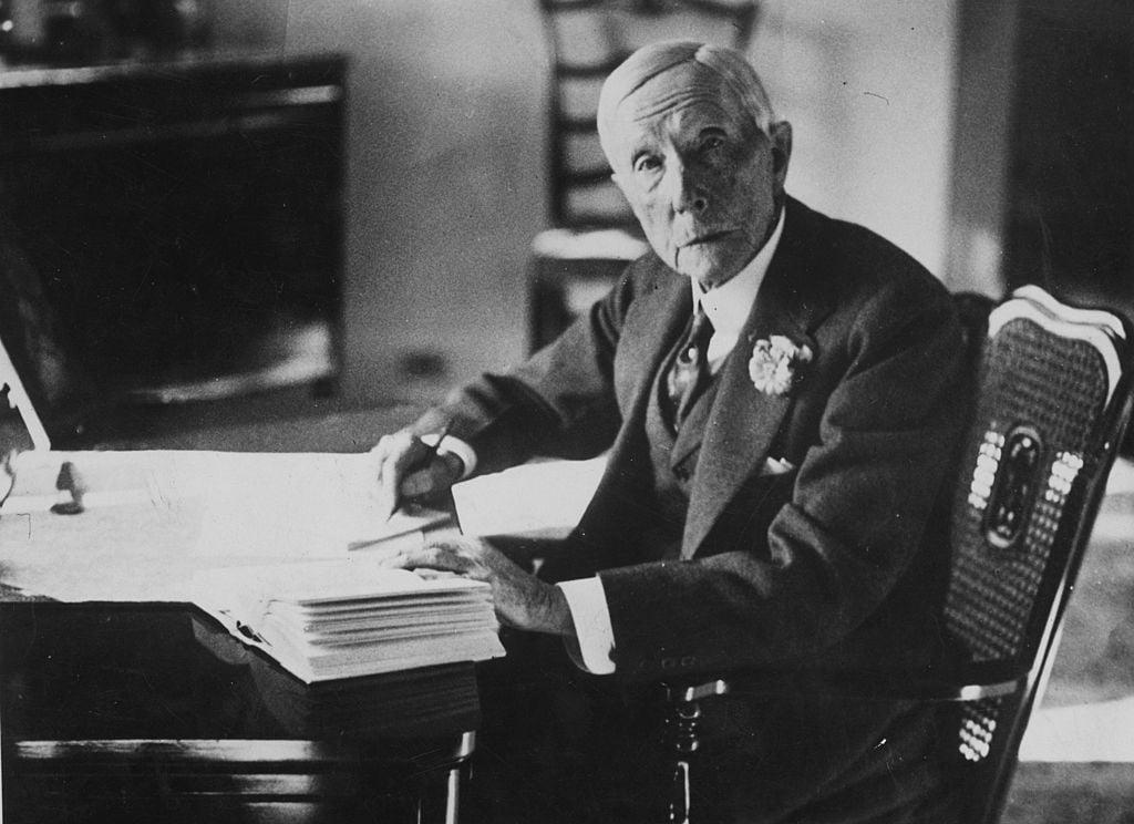 American industrialist J D Rockefeller (John Davidson Rockefeller, 1839 - 1937) working on a document at his desk.