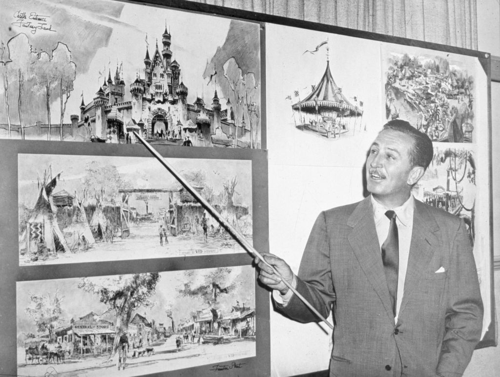 American producer, director, and animator Walt Disney (1901 - 1966) uses a baton to point to sketches of Disneyland, 1955.