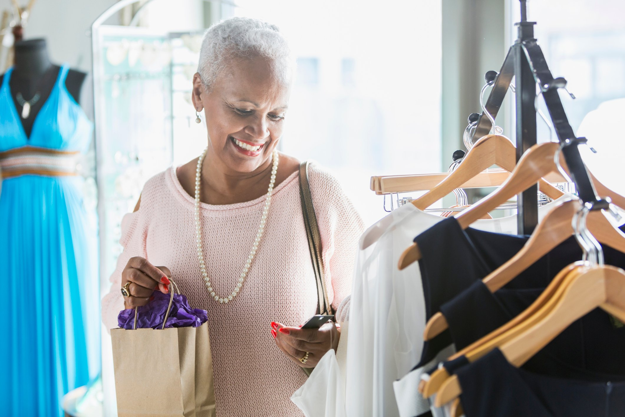 A senior African American woman shopping in a clothing store. She is standing by a rack of dresses on hangers, looking at a price tag, carrying a shopping bag.