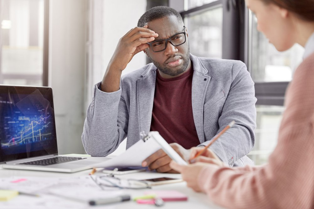 confused man at work listening to coworker explain concept