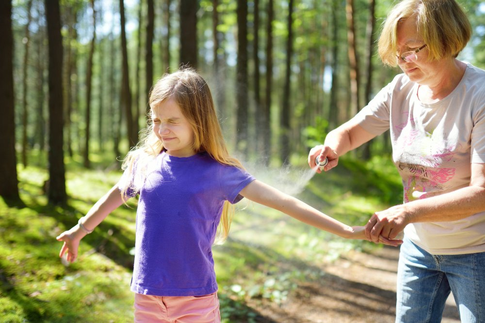 grandmother spraying her young granddaughter with insect repellant