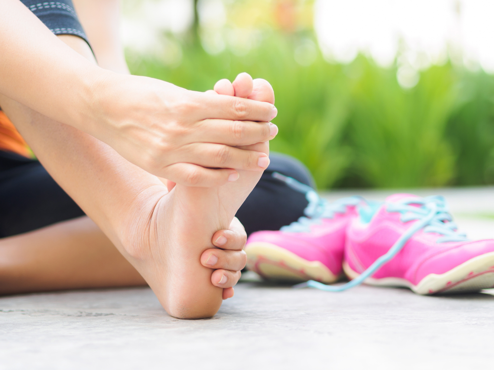 person holding their sore foot