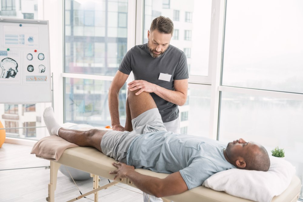 physical therapist working on a patient's leg mobility