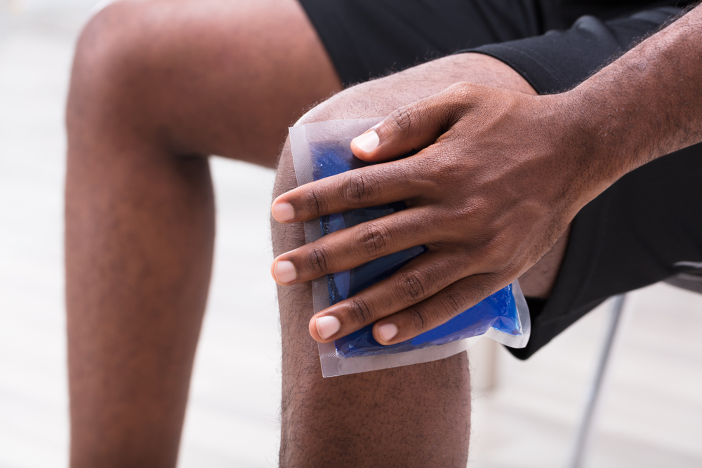 man holding an ice pack to his sore knee