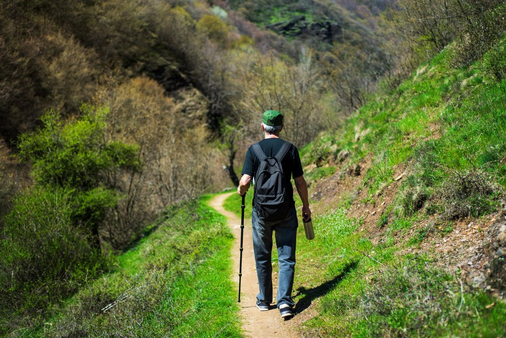 older man hiking with a cane
