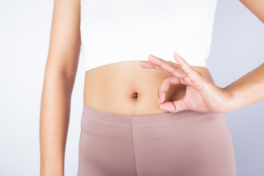 healthy gut concept; woman with ok fingers by stomach