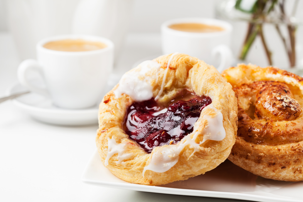 two sugary pastries in foreground with coffee