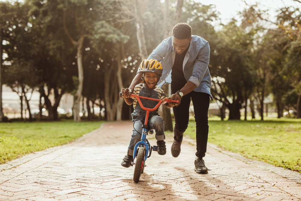 dad helping his young son ride a bike
