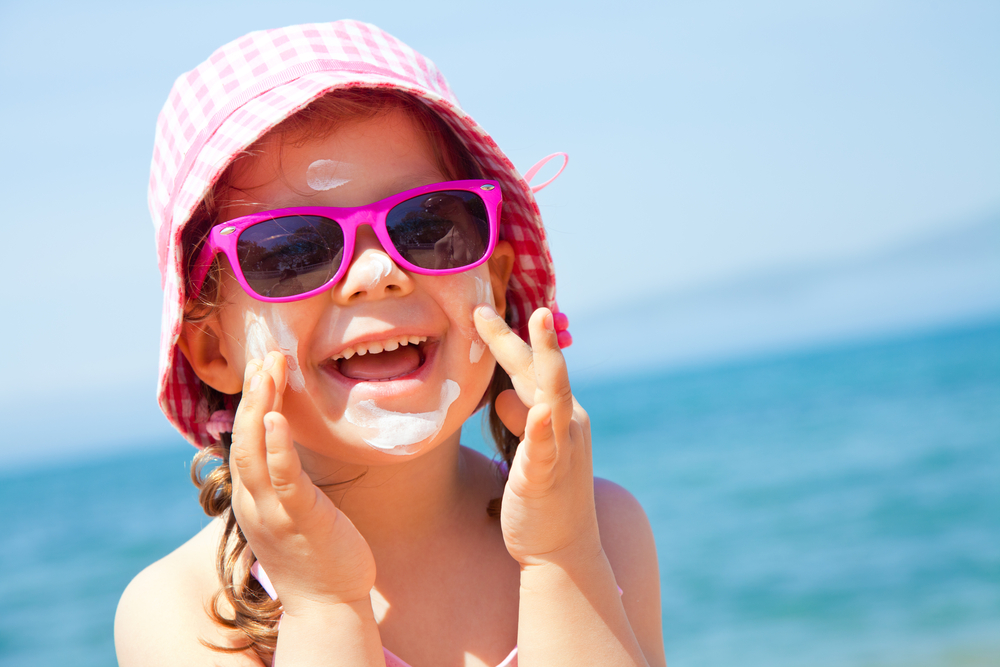 little girl with sunscreen and a sun hat at the beach