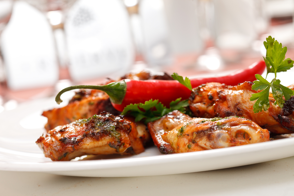 plate of spicy chicken wings and peppers