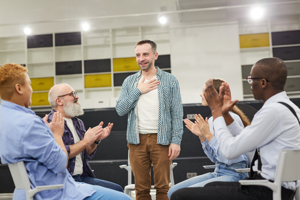 man speaking in recovery support group