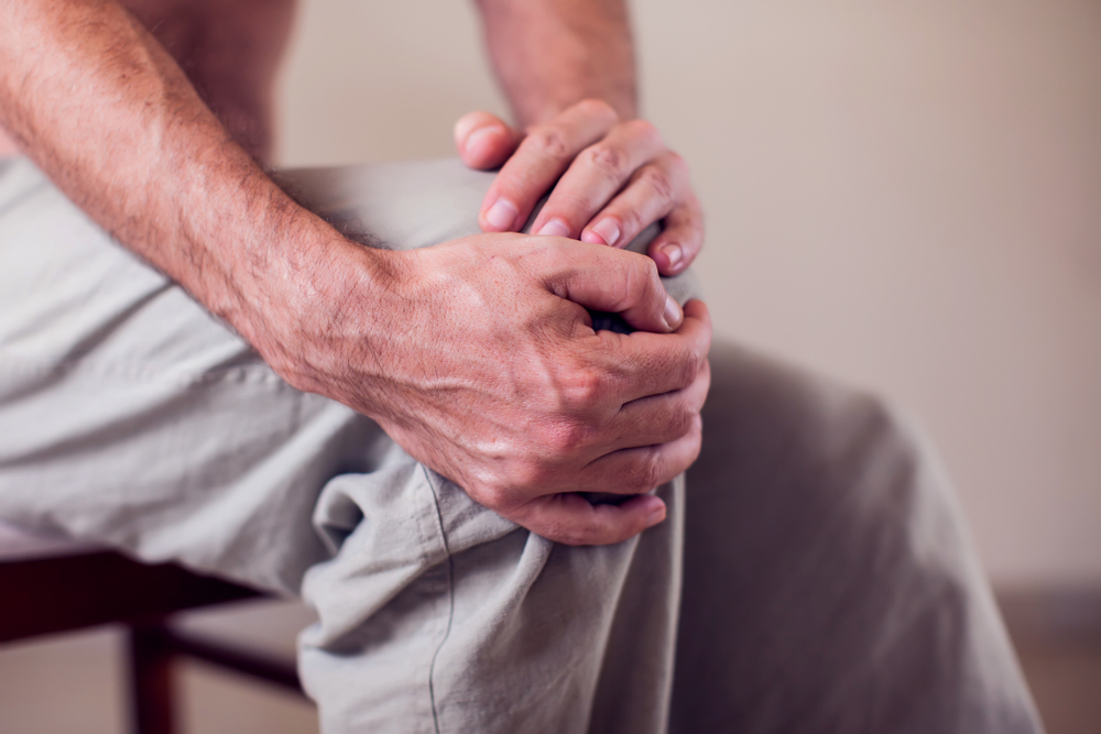 man holding his knee, knee pain or arthritis concept