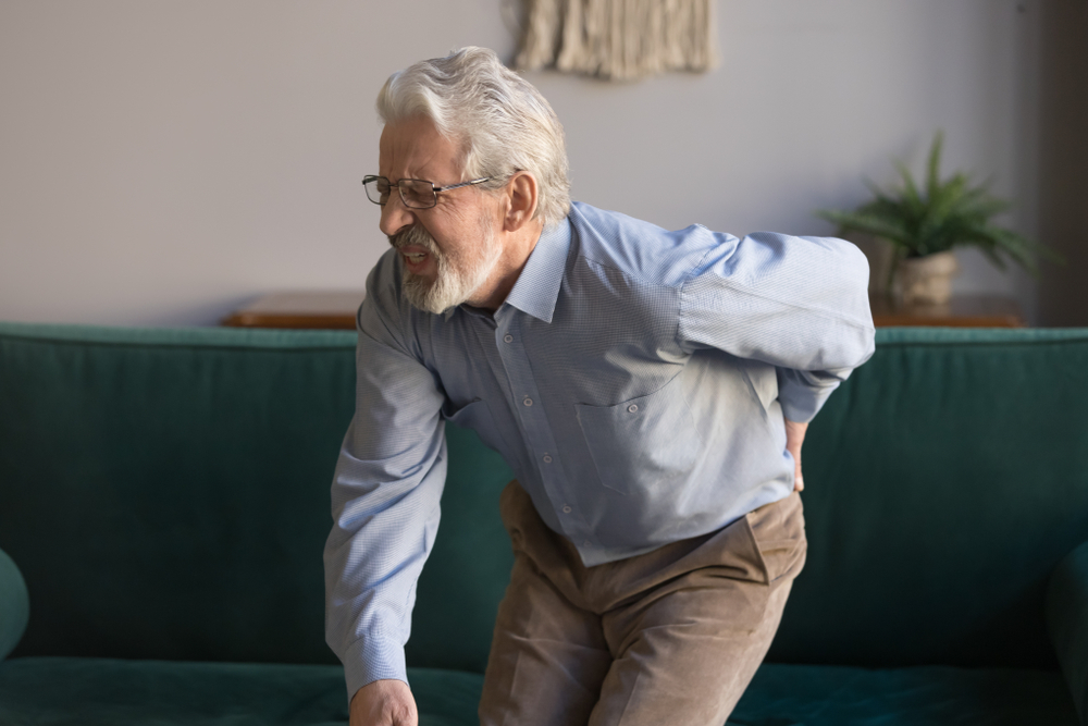 older man with sudden back pain standing up