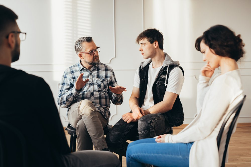 therapist speaking to young man in therapy group