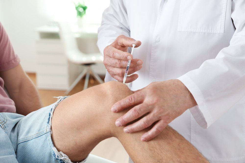 doctor injecting needle into patient's knee