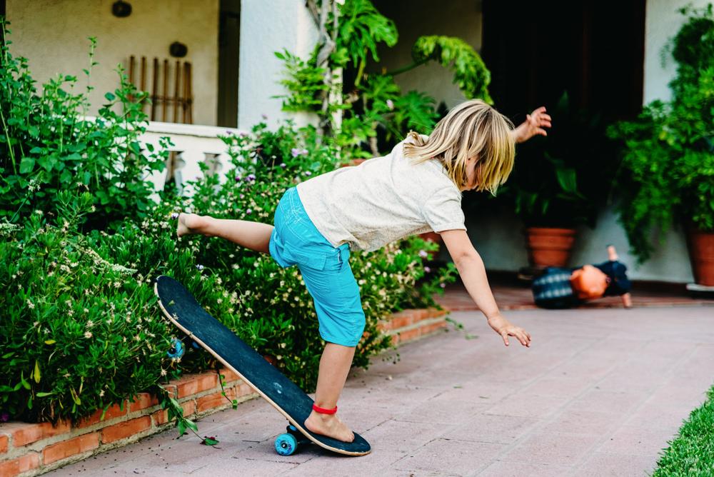 little boy falling off his skateboard