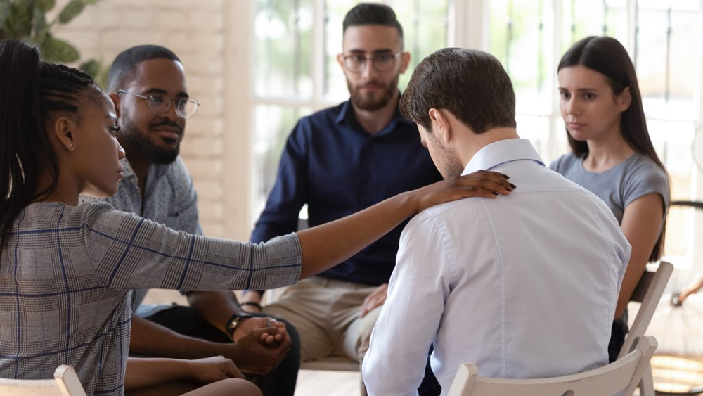 woman comforting another member of group therapy program