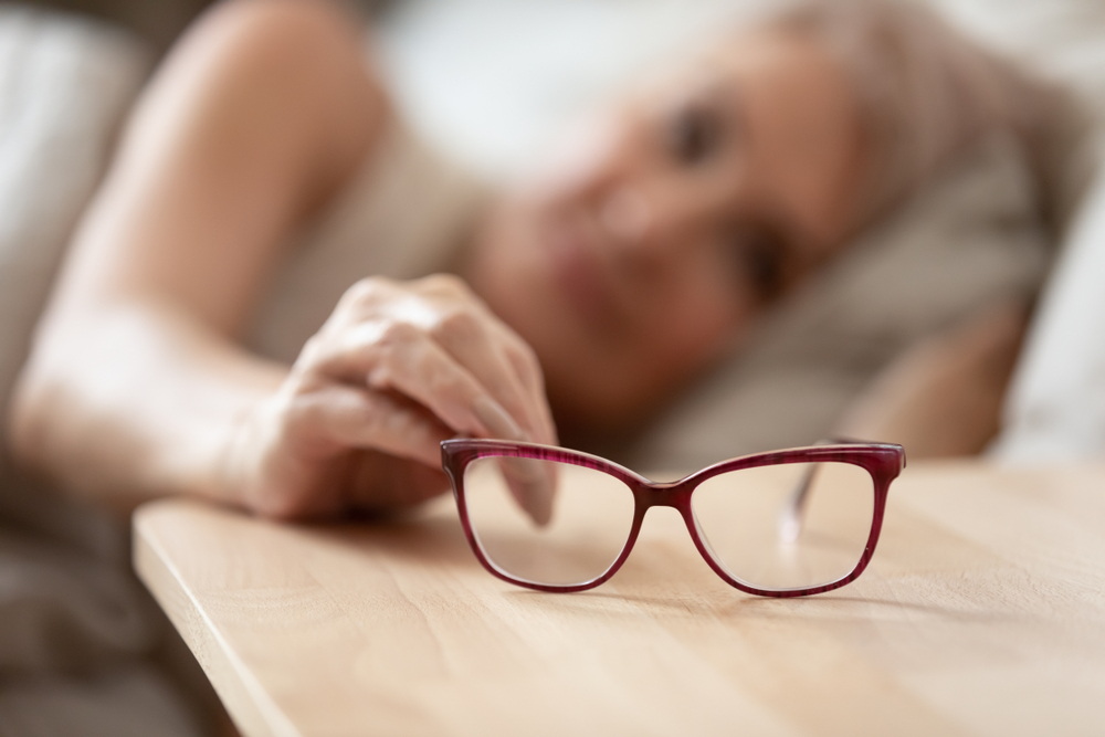 older woman blurry reaching for glasses in focus