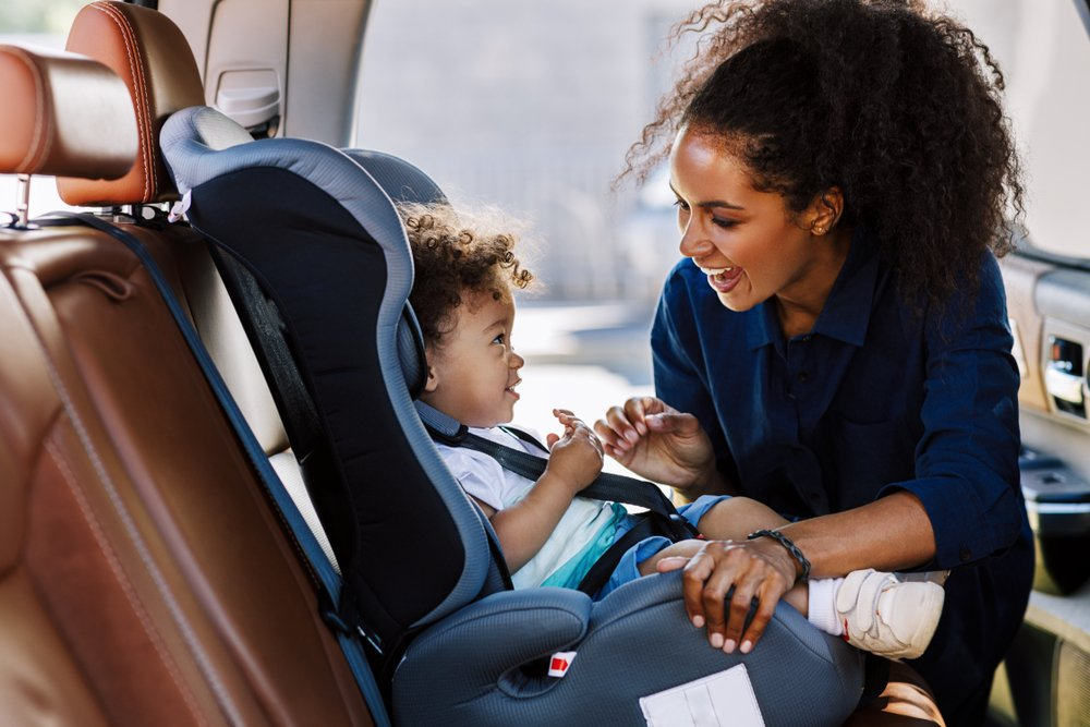 mom buckling her toddler into his car seat
