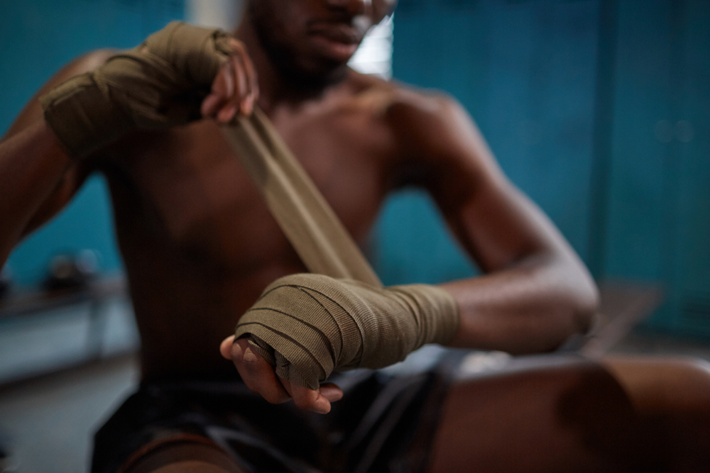 young boxer wrapping his hand before fight