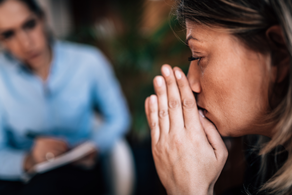 sad, worried woman speaking with therapist