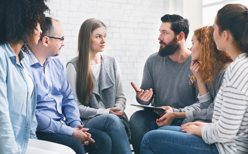 leader speaking in a group therapy session