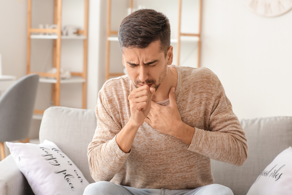 man on couch coughing