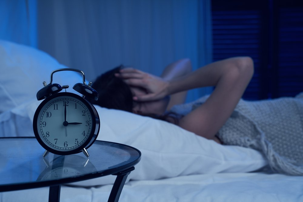 woman in bed can't sleep at 3 o'clock in the morning