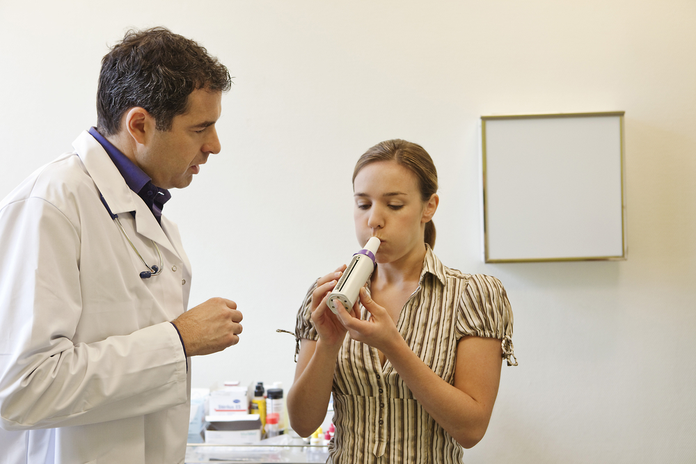 patient breathing into a spirometer at doctor's office