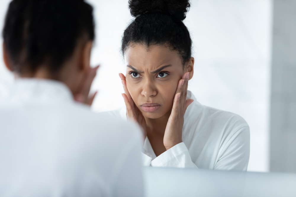 unhappy woman frowning at her reflection