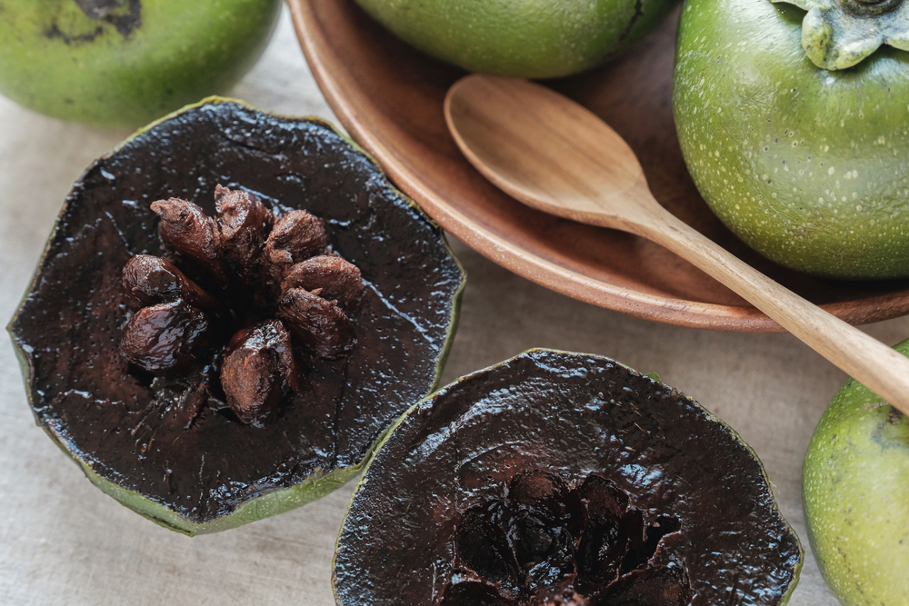 black sapote fruit cut in half on table