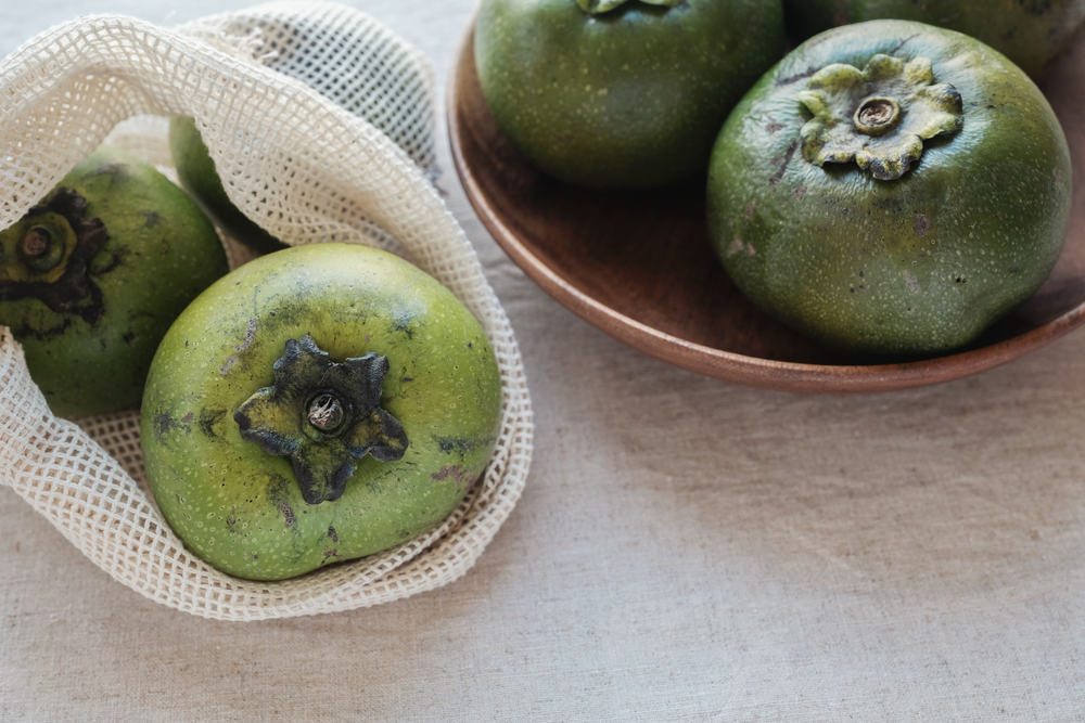 unsliced black sapote fruits on a table