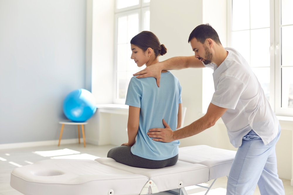 medical practitioner examining patient's sore back